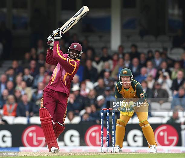 Chris Gayle of West Indies hits over long off with Brad Haddin of Australia looking on during the ICC Twenty20 World Cup match between Australia and...