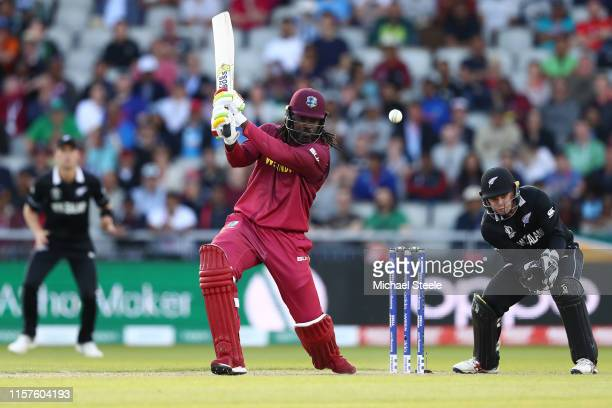 Chris Gayle of West Indies hits to the offside as New Zealand wicketkeeper Tom Latham looks on during the Group Stage match of the ICC Cricket World...