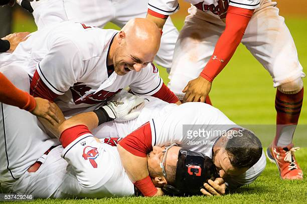 Chris Gimenez and Jason Kipnis celebrate with Yan Gomes of the Cleveland Indians after Gomes hit a walkoff RBI single in the eleventh inning to...