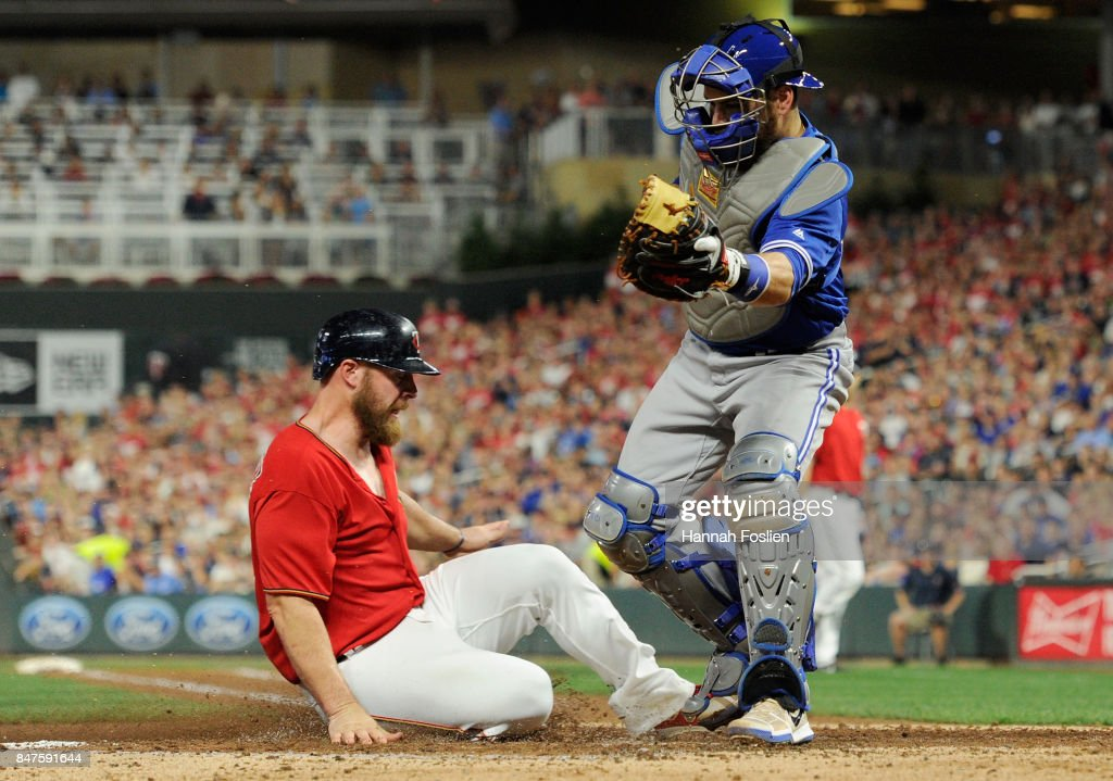 Chris Gimenez #38 of the Minnesota Twins slides safely into home plate against Russell Martin #55 of the Toronto Blue Jays to score a run during the third inning of the game on September 15, 2017 at Target Field in Minneapolis, Minnesota.