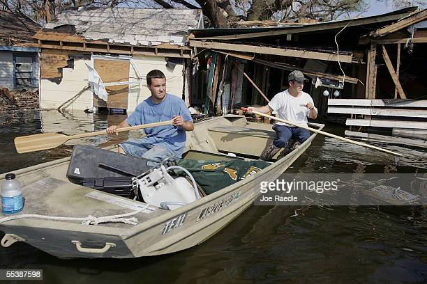 Chris Glass and Dwayne Glass paddle away after getting a first hand look at their mother's house which was destroyed by Hurricane Katrina September...