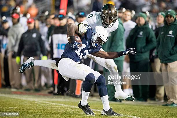 Chris Godwin of the Penn State Nittany Lions fights to make a catch in bounds as Montae Nicholson of the Michigan State Spartans makes the tackle...