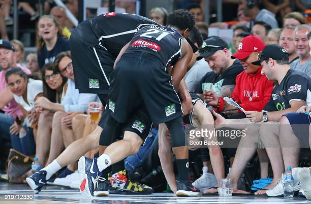 Chris Goulding of Melbourne United is helped up by his teammates after sliding into the crowd during the round 19 NBL match between Melbourne United...