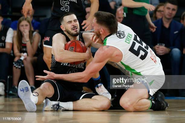 Chris Goulding of United and Mitch Creek of the Phoenix contest the ball during the round one NBL match between Melbourne United and the South East...