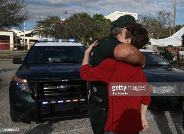 Chris Grady a senior at Marjory Stoneman Douglas High School hugs Broward County Sheriff officer Brad Griesinger as he guards the front gate of the...
