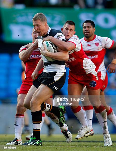 Chris Green of Hull FC is tackled by Michael Dobson and Greg Green of Hull KR during the Super League Magic Weekend match between Hull FC and Hull...