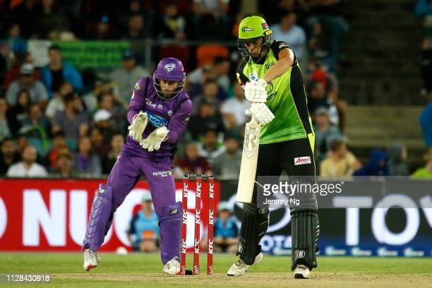 Chris Green of the Thunder bats as Matthew Wade of the Hurricanes wicketkeeps during the Big Bash League match between the Sydney Thunder and the...