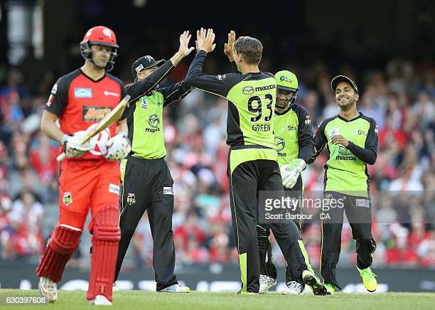 Chris Green of the Thunder is congratulated by his teammates after dismissing Cameron White of the Renegades during the Big Bash League match between...