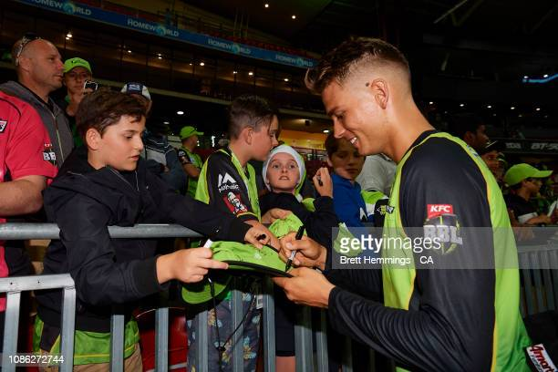 Chris Green of the Thunder signs an autography during the Sydney Thunder v Sydney Sixers Big Bash League Match at Spotless Stadium on December 24...