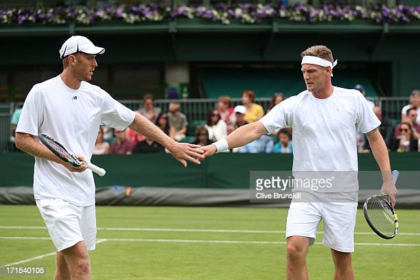 Chris Guccione and Samuel Groth of Australia tap hands during their Gentlemen's Doubles first round match against Steve Johnson of the United States...