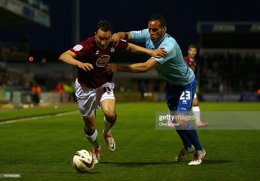 Chris Hackett of Northampton Town is tackled by Kaid Mohamed of Cheltenham Town during the npower League Two Play Off Semi Final First Leg match between Northampton Town and Cheltenham Town at Sixfields on May 2, 2013 in Northampton, England.