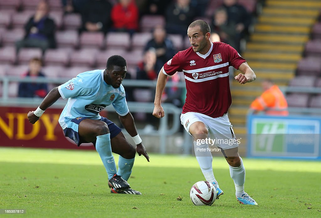 Chris Hackett of Northampton Town looks to move forward with the ball watched by Femi Ilesanmi of Dagenham & Redbridge during the Sky Bet League Two match between Northampton Town and Dagenham & Redbridge at Sixfields Stadium on October 19, 2013 in Northampton, England.