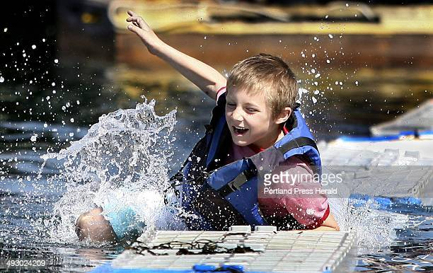 Chris Hamlet falls into the water after making it across 17 crates during the lobster crate running competition at the 37th annual Fishermen's...
