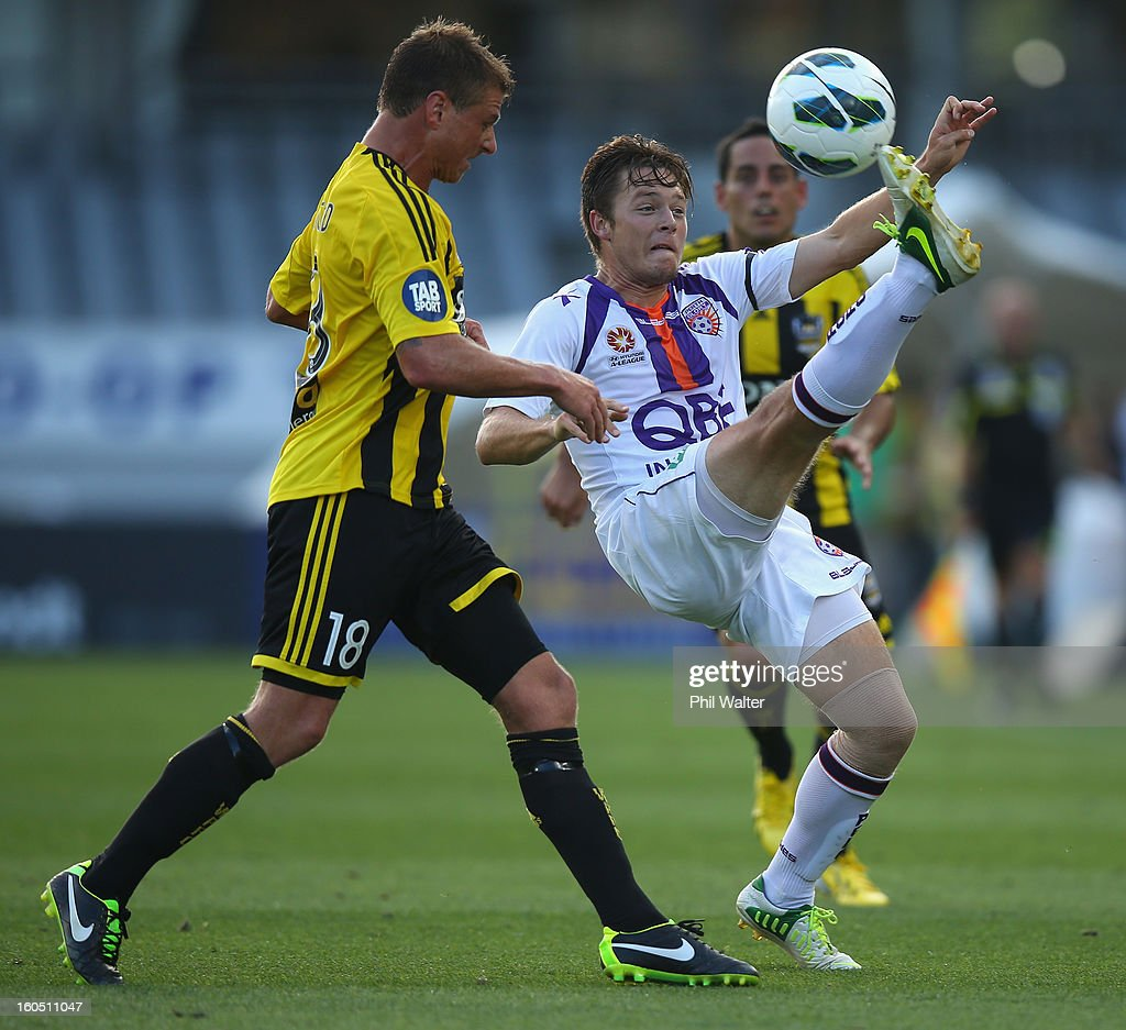 Chris Harold of Perth clears the ball under pressure from Ben Sigmund of the Phoenix during the round 19 A-League match between the Wellington Phoenix and the Perth Glory at Eden Park on February 2, 2013 in Auckland, New Zealand.