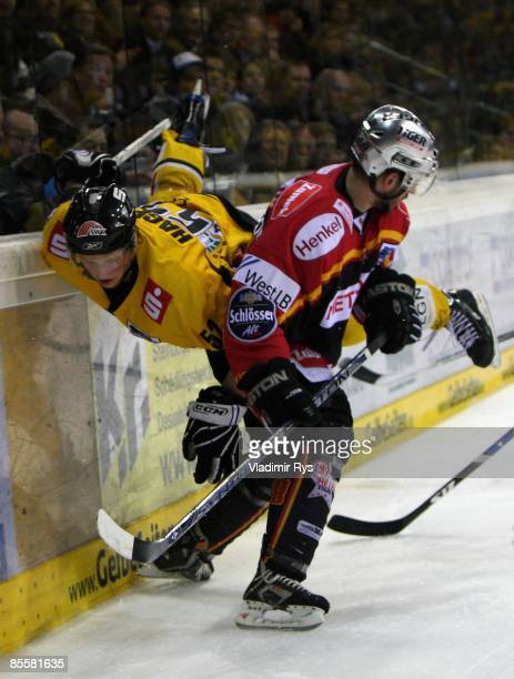 Chris Harrington of Metro Stars body checks Patrick Hager of Pinguine during the DEL sixth quarter final play-off game between Krefeld Pinguine and...