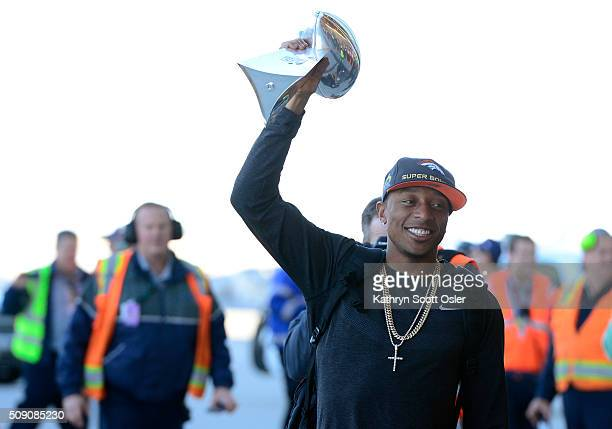 Chris Harris holds up the Vince Lombardi Trophy as members of the Denver Broncos football team arrive home at Denver international Airport on Monday...