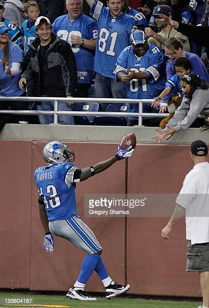 Chris Harris of the Detroit Lions hands the ball to a fan after he intercepted a fourth quarter pass while playing the Carolina Panthers at Ford...