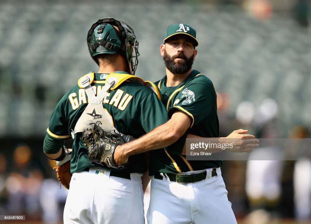 Chris Hatcher #44 and Dustin Garneau #12 of the Oakland Athletics congratulate one another after they beat the Los Angeles Angels at Oakland Alameda Coliseum on September 6, 2017 in Oakland, California.