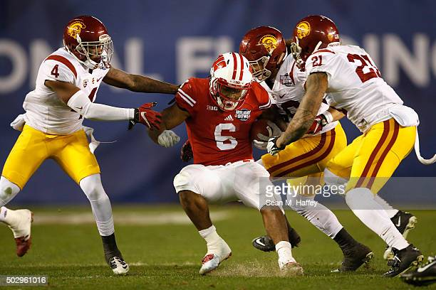 Chris Hawkins of the USC Trojans Su'a Cravens of the USC Trojans Osa Masina of the USC Trojans tackle Corey Clement of the Wisconsin Badgers during...