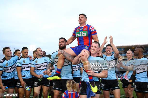 Chris Heighington of the Knights is chaired off the field by former Sharks team mates Andrew Fifita of the Sharks and Paul Gallen of the Sharks...
