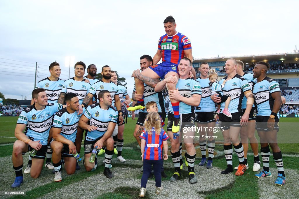 Chris Heighington of the Knights is chaired off the field by former Sharks team mates Andrew Fifita of the Sharks and Paul Gallen of the Sharks following the round 24 NRL match between the Cronulla Sharks and the Newcastle Knights at Southern Cross Group Stadium on August 26, 2018 in Sydney, Australia.