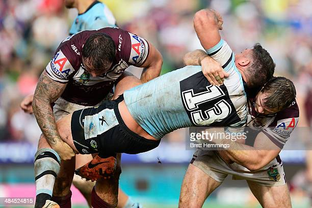 Chris Heighington of the Sharks is lifted into a heavy tackle by Anthony Watmough and Brenton Lawrence of the Sea Eagles during the round 6 NRL match...