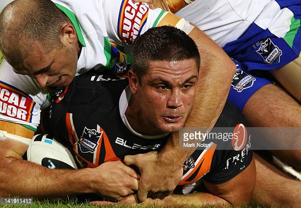Chris Heighington of the Tigers is tackled during the round four NRL match between the Wests Tigers and the Canberra Raiders at Campbelltown Sports...