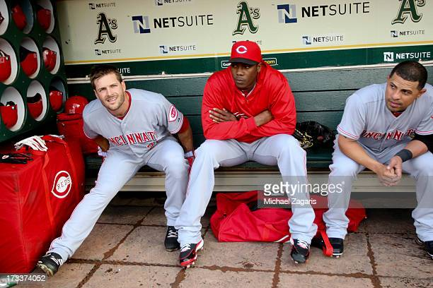 Chris Heisey Aroldis Chapman and Xavier Paul of the Cincinnati Reds relax in the dugout prior to the game against the Oakland Athletics at Oco...
