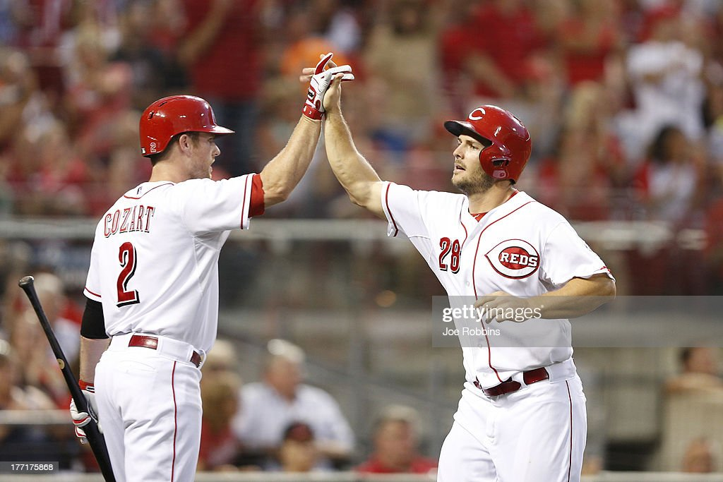 Chris Heisey #28 of the Cincinnati Reds celebrates with teammate Zack Cozart #2 after scoring a run in the third inning of the game against the Arizona Diamondbacks at Great American Ball Park on August 21, 2013 in Cincinnati, Ohio.