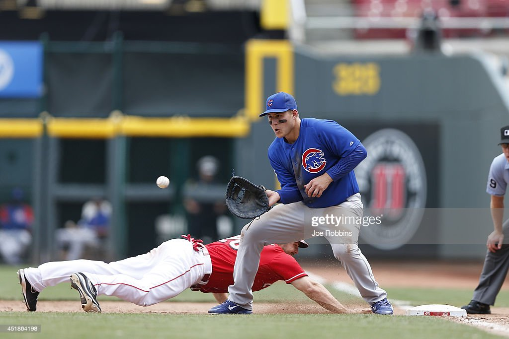 Chris Heisey #28 of the Cincinnati Reds dives back to first base ahead of the pickoff throw to Anthony Rizzo #44 of the Chicago Cubs during the game at Great American Ball Park on July 8, 2014 in Cincinnati, Ohio. The Reds won 4-2.