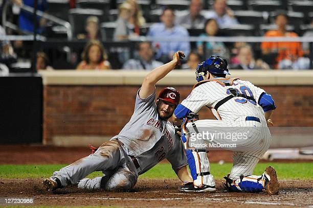 Chris Heisey of the Cincinnati Reds scores a run beating the tag from Josh Thole of the New York Mets in the fourth inning of a game at Citi Field on...