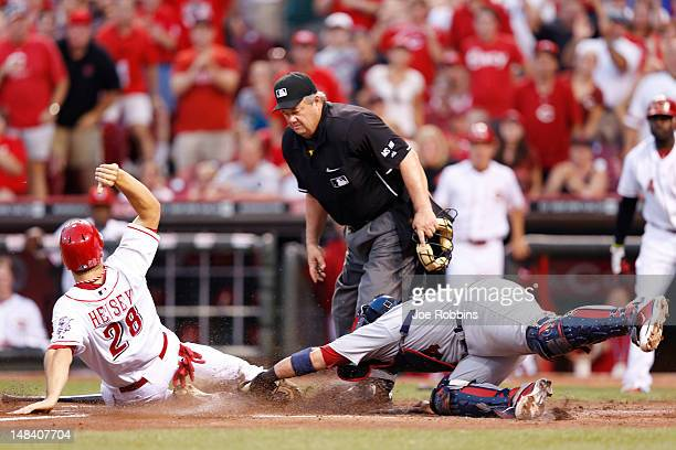 Chris Heisey of the Cincinnati Reds slides ahead of the tag by Yadier Molina of the St Louis Cardinals to score the tying run after a double by Joey...