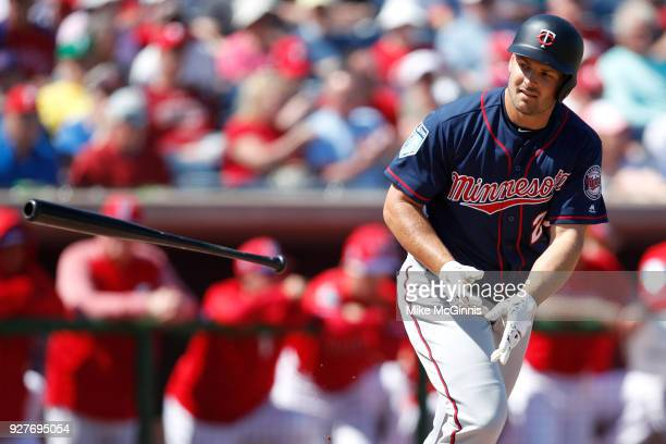 Chris Heisey of the Minnesota Twins throws his bat after drawing a walk during the second inning of the spring training game against the Philadelphia...