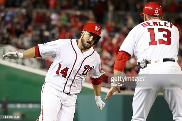 Chris Heisey of the Washington Nationals celebrates with third base coach Bob Henley after hitting a two run home run in the seventh inning against...
