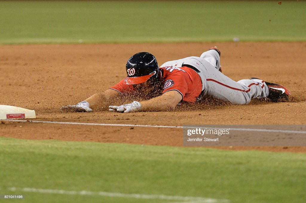 Chris Heisey #14 of the Washington Nationals slides into a triple against the Arizona Diamondbacks in the sixth inning at Chase Field on July 22, 2017 in Phoenix, Arizona.