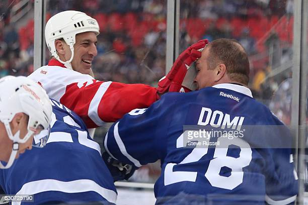 TORONTO ON DECEMBER 31 Chris Helios give Tie Domi a little leather as the Toronto Maple Leafs alumni play the Detroit Red Wings alumni on the eve of...