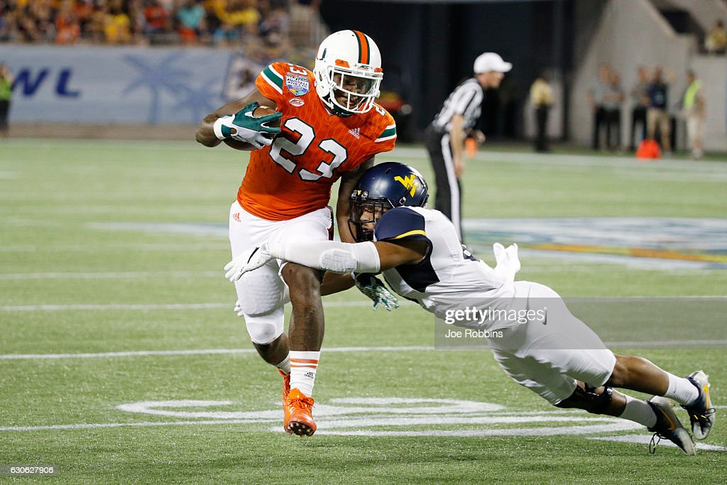 Chris Herndon IV #23 of the Miami Hurricanes gets tackled after a reception against the West Virginia Mountaineers in the second half of the Russell Athletic Bowl at Camping World Stadium on December 28, 2016 in Orlando, Florida. Miami defeated West Virginia 31-14.