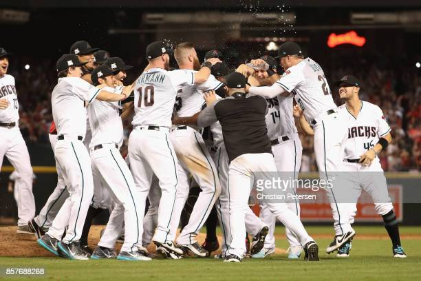 Chris Herrmann and Brandon Drury of the Arizona Diamondbacks celebrate with teammates after defeating the Colorado Rockies 11-8 in the National...