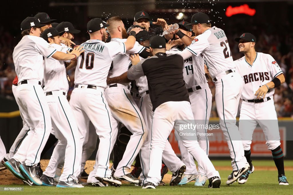 Chris Herrmann #10 and Brandon Drury #27 of the Arizona Diamondbacks celebrate with teammates after defeating the Colorado Rockies 11-8 in the National League Wild Card game at Chase Field on October 4, 2017 in Phoenix, Arizona.