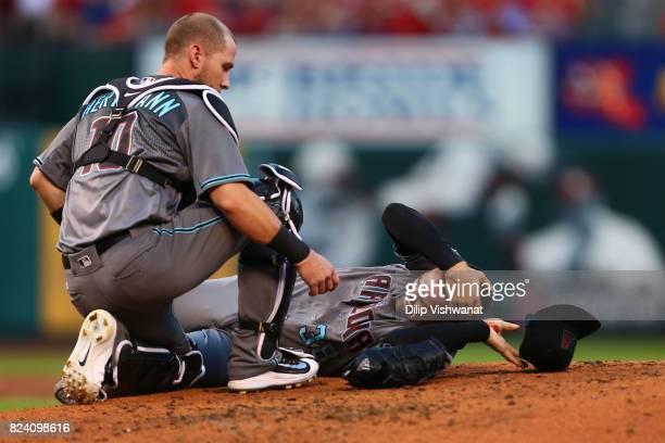 Chris Herrmann of the Arizona Diamondbacks comes to the aid of pitcher Robbie Ray of the Arizona Diamondbacks after he was hit in the head by a line...