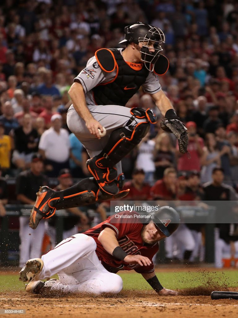 Chris Herrmann #10 of the Arizona Diamondbacks is forced out at home plate by catcher J.T. Realmuto #11 of the Miami Marlins during the ninth inning of the MLB game at Chase Field on September 24, 2017 in Phoenix, Arizona. The Diamondbacks defeated the Marlins 3-2.