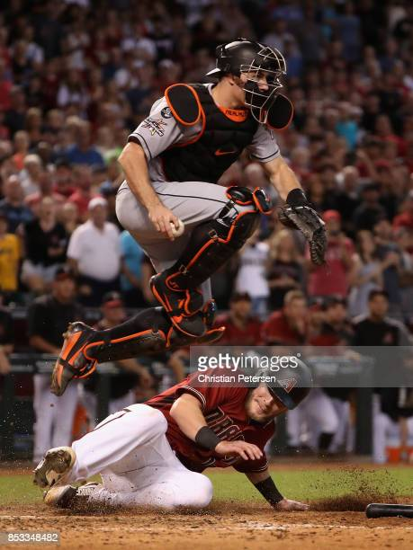 Chris Herrmann of the Arizona Diamondbacks is forced out at home plate by catcher JT Realmuto of the Miami Marlins during the ninth inning of the MLB...