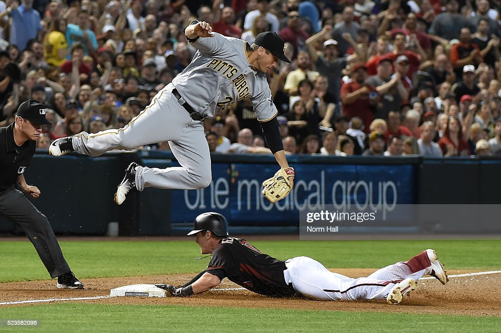 Chris Herrmann #10 of the Arizona Diamondbacks safely slides into third base under a leaping David Freese #23 of the Pittsburgh Pirates during the second inning at Chase Field on April 23, 2016 in Phoenix, Arizona.