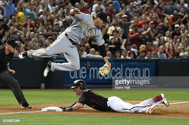 Chris Herrmann of the Arizona Diamondbacks safely slides into third base under a leaping David Freese of the Pittsburgh Pirates during the second...