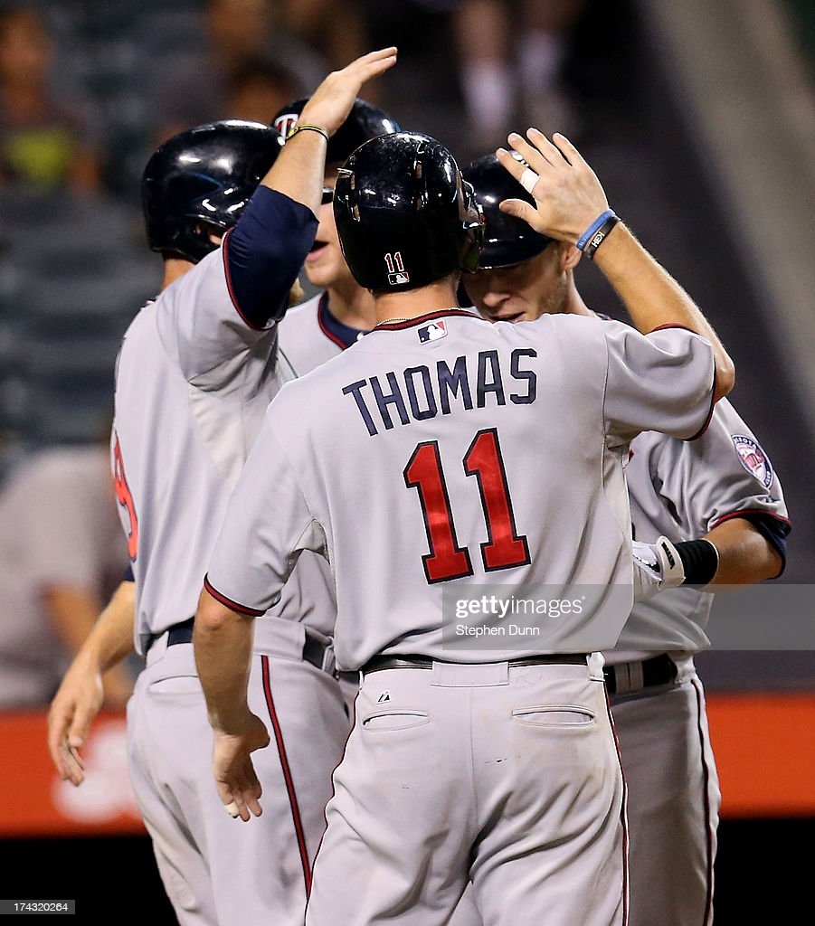Chris Herrmann #12 (L) of the Minnesota Twins celebrates with Justin Morneau #33, Clete Thomas #11, and Ryan Doumit #9 after they all score on Herrmann's grand slam home run in the 10th inning against the Los Angeles Angels of Anaheim at Angel Stadium of Anaheim on July 23, 2013 in Anaheim, California.