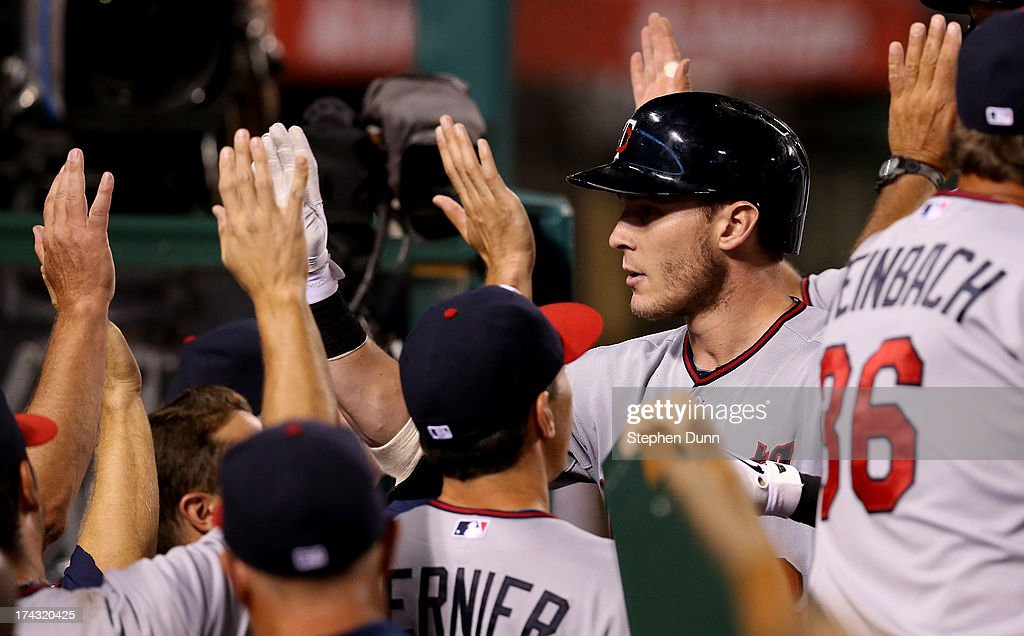 Chris Herrmann #12 of the Minnesota Twins is greeted by teammates as he returns to the dugout after hitting a grand slam home run in the 10th inning against the Los Angeles Angels of Anaheim at Angel Stadium of Anaheim on July 23, 2013 in Anaheim, California.