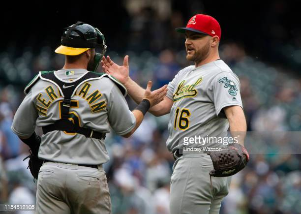 Chris Herrmann of the Oakland Athletics greets Liam Hendriks to celebrate their 74 victory over the Settle Mariners at TMobile Park on July 7 2019 in...