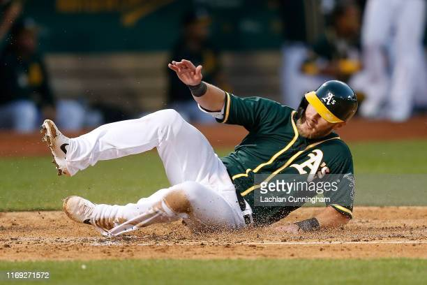 Chris Herrmann of the Oakland Athletics slides in safe at home plate to score on a double hit by Marcus Semien in the bottom of the second inning...