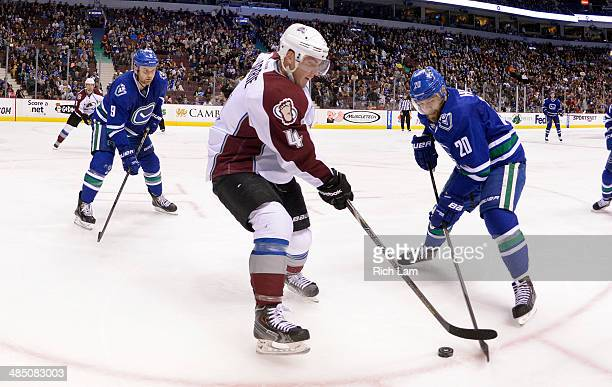 Chris Higgins and Zack Kassian of the Vancouver Canucks try to check Tyson Barrie of the Colorado Avalanche during NHL action on April 10 2014 at...