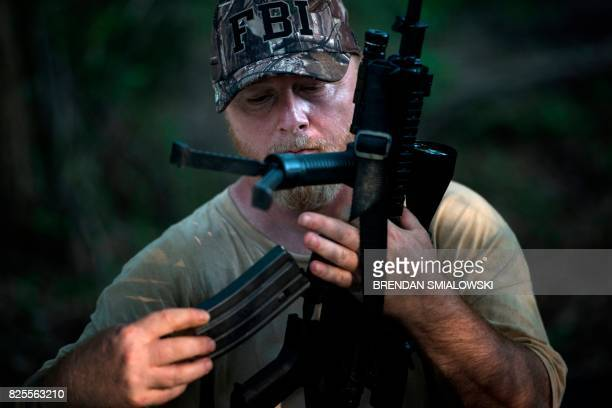 Chris Hill founder of the Georgia Security Force III% militia loads a rifle during a field training exercise July 29 2017 in Jackson Georgia / AFP...